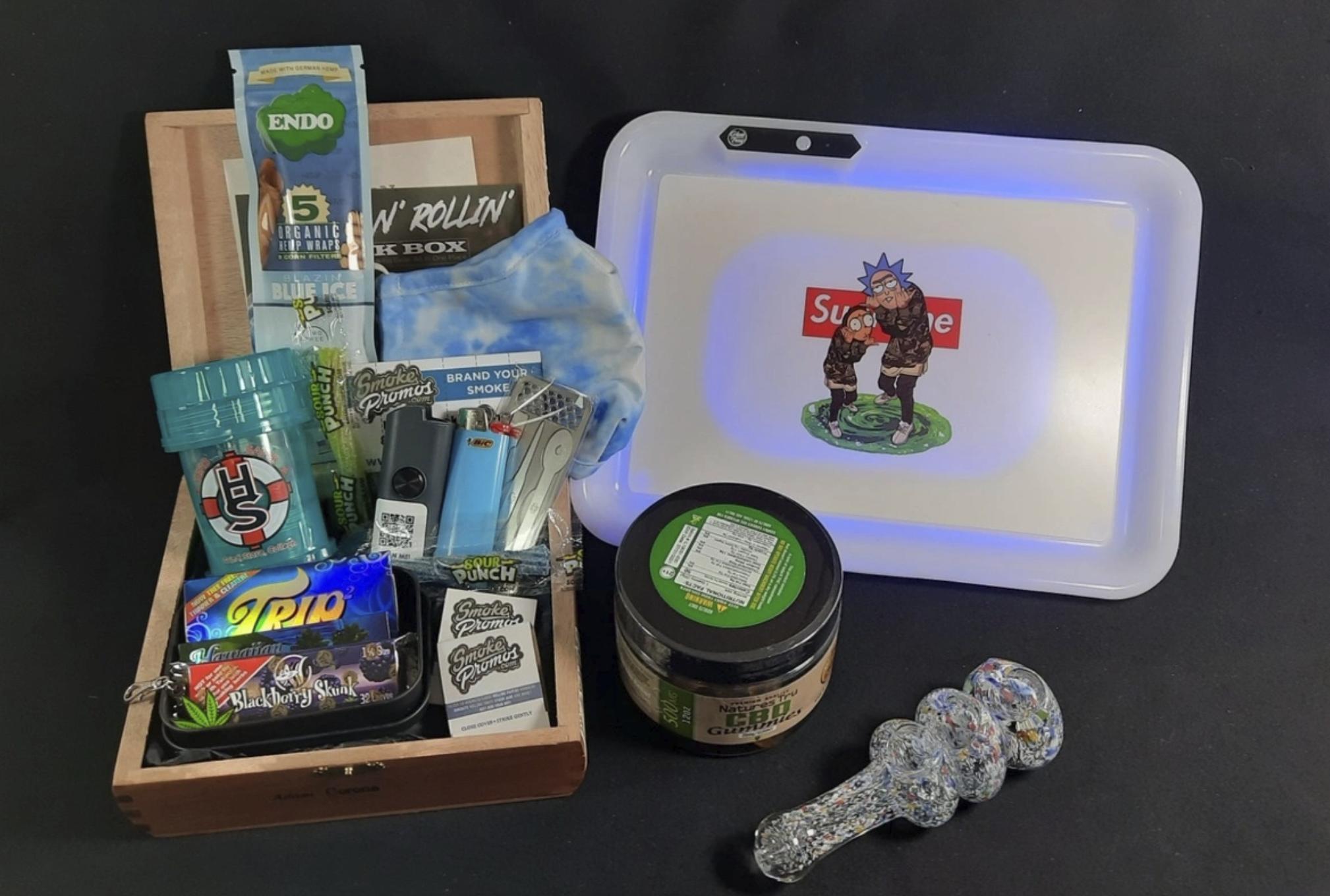 the subscripiton box with CBD gummies, a glass pipe, a rolling tray, rolling papers, lighters, and more