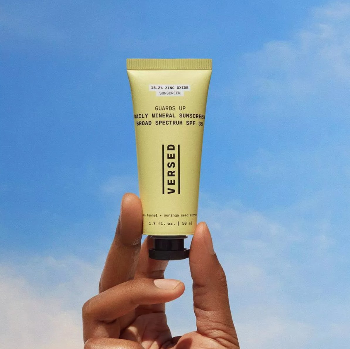 The Versed daily mineral sunscreen in a yellow bottle being held up in front of the sky