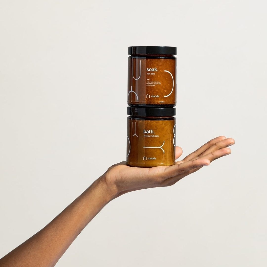 Two jars of the bath products stacked on top of one another on a person's hand