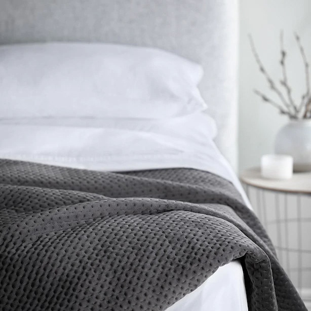 A weighted blanket on the bottom half of a bed
