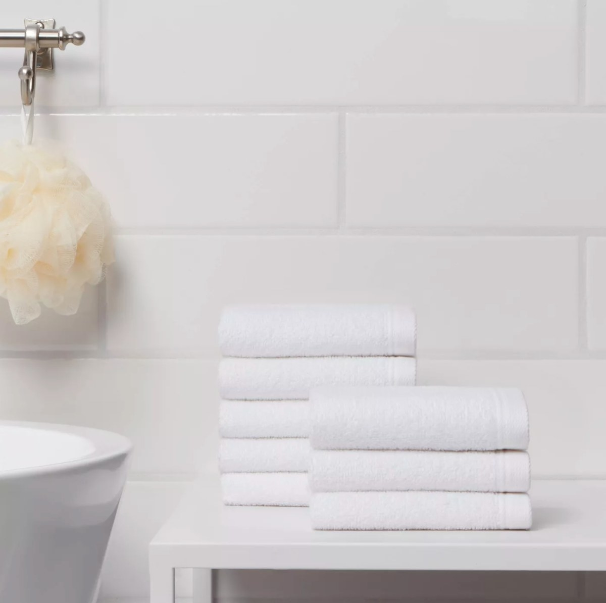 The bath towel set in white on a bathroom counter next to a loofa
