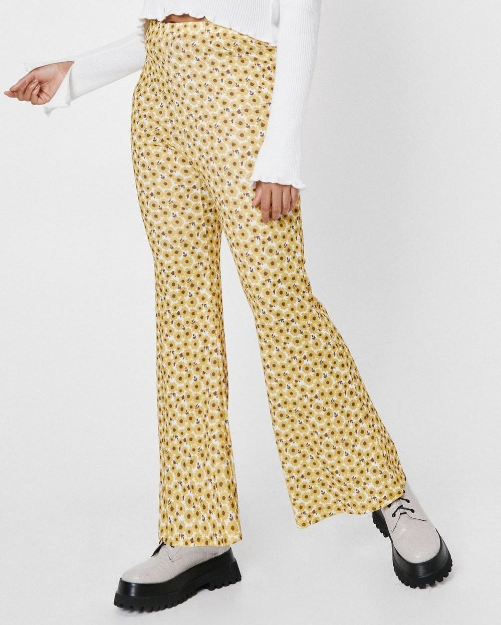 a pair of pants that flare toward the bottom with daisies patterned all over