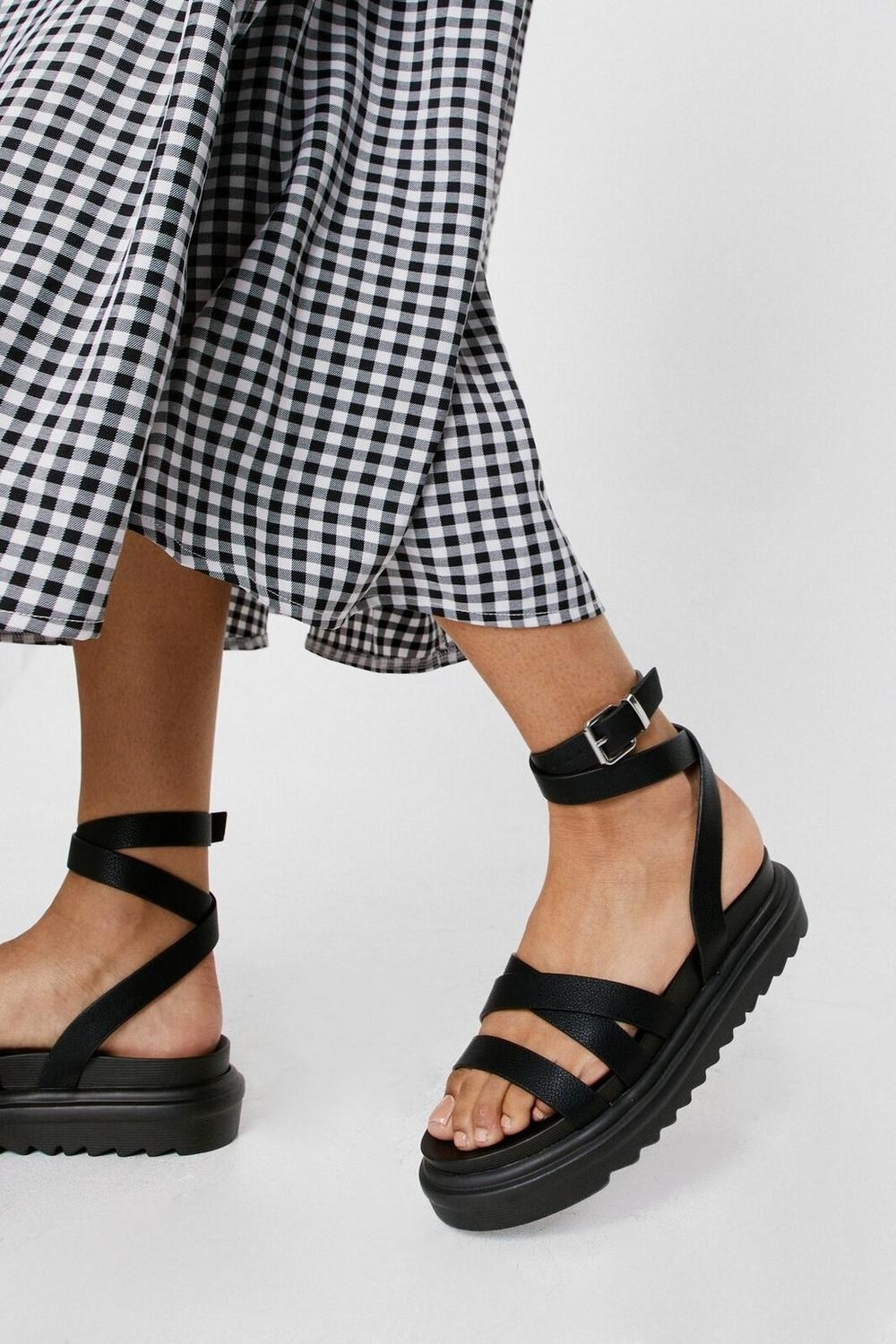 a pair of platform sandals with straps that attach around the ankles