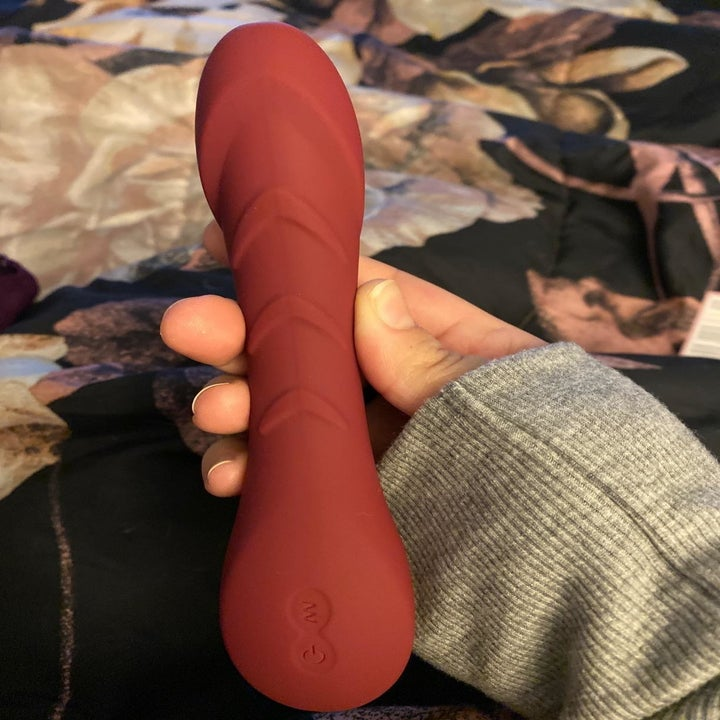 same reviewer holding the burgundy MELO vibrating dildo up, showing its underside which has V shapes running down the shaft