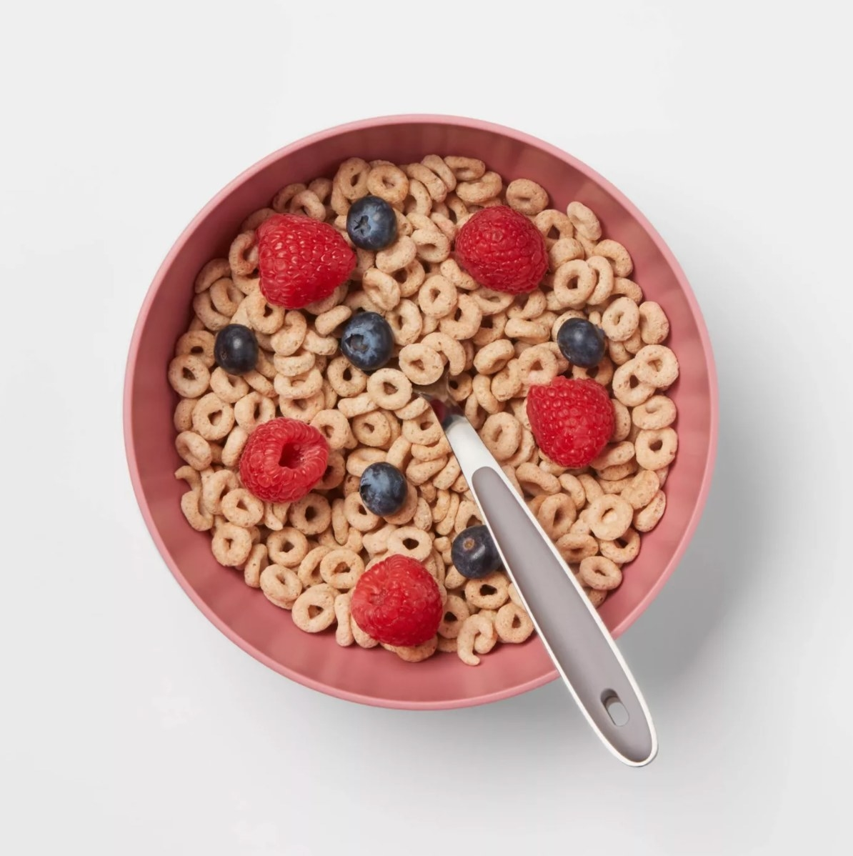 The cereal bowl in coral holding Cheerios with raspberries and blueberries