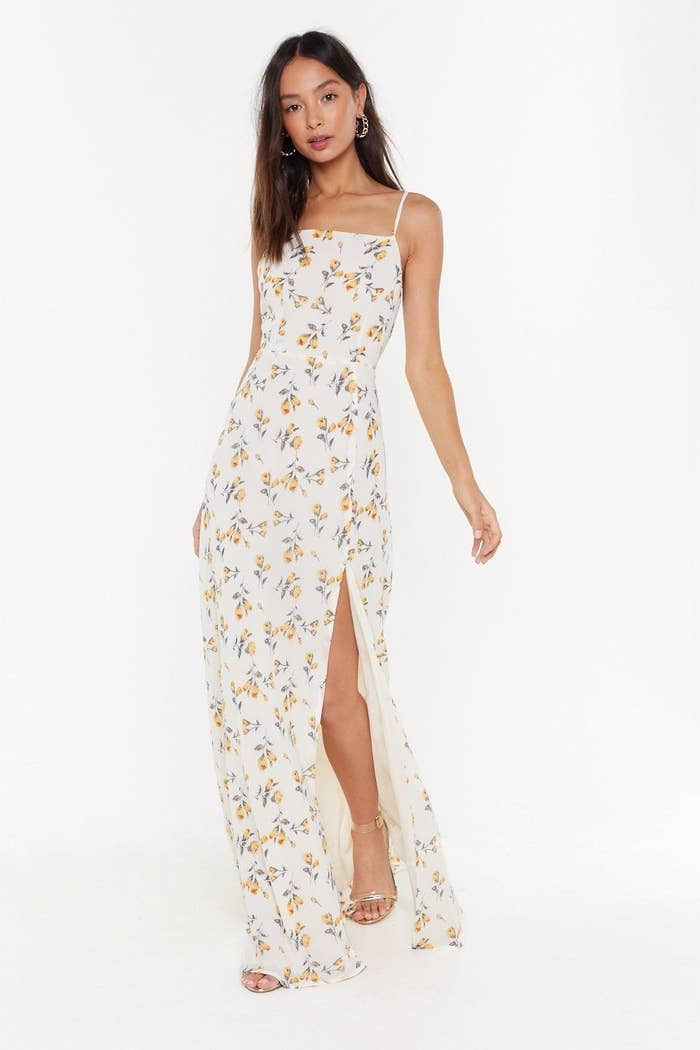 A person wearing a maxi floral dress with a box neck and slit up one leg