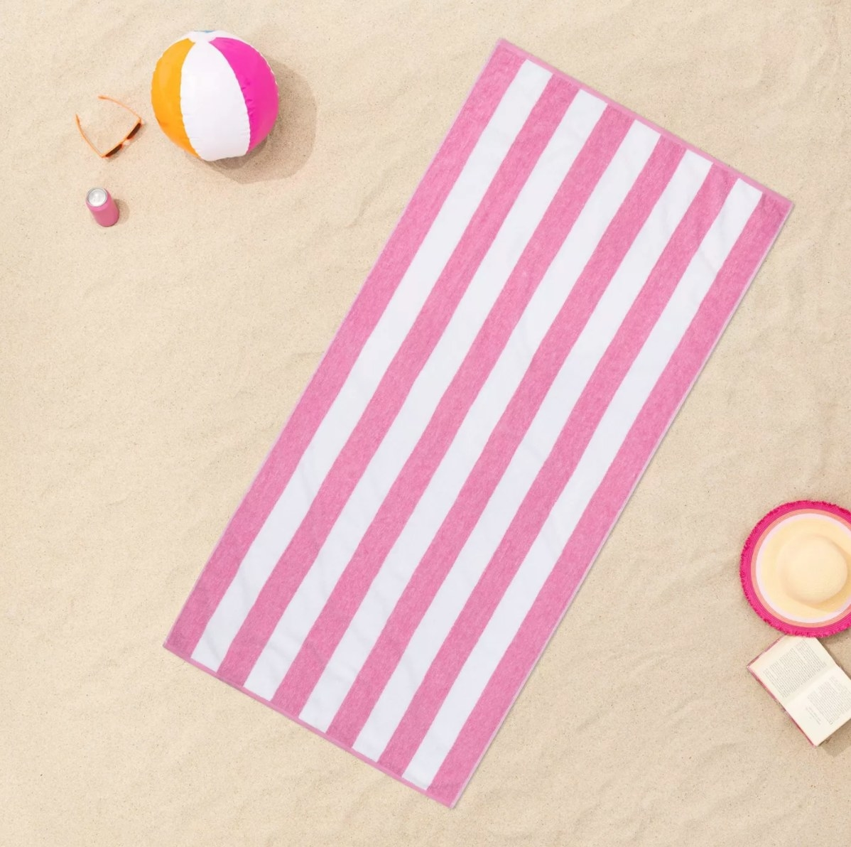 The striped beach towel in pink with white stripes with a beach ball, glasses, and a drink next to it