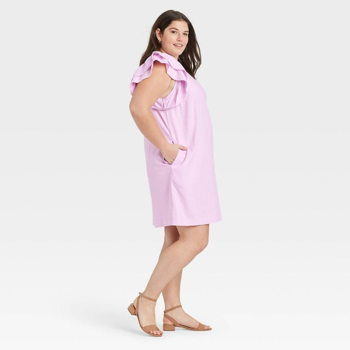 Model wearing light pink dress with ruffle sleeves, stops above knees