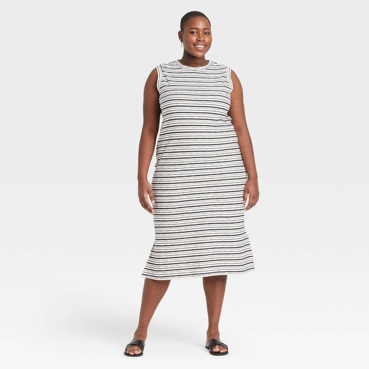 Model white dress with black stripes, goes past the knee
