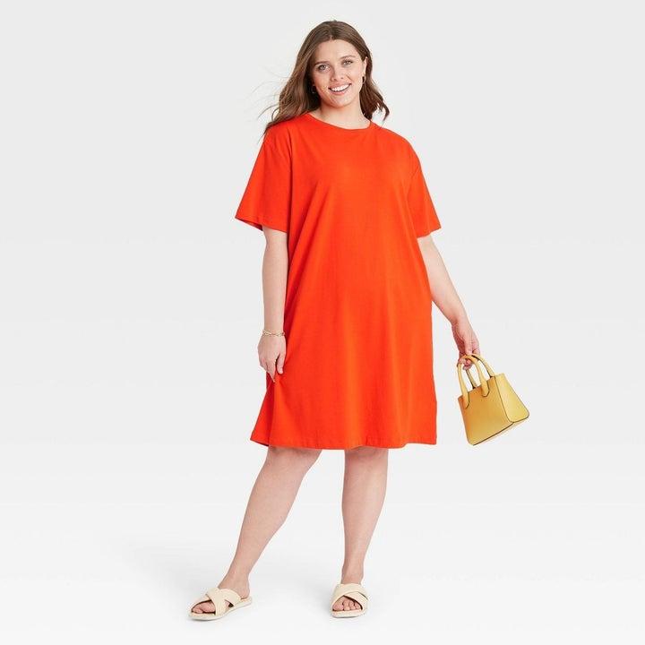 Model wearing short sleeve orange dress, goes slightly past the knees
