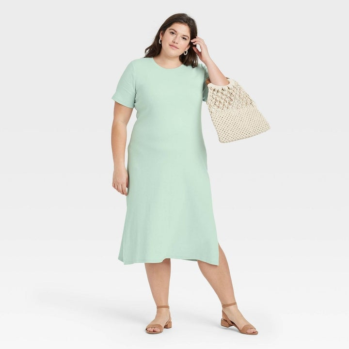 Model wearing sea green dress with two slits on both sides, goes past the knee
