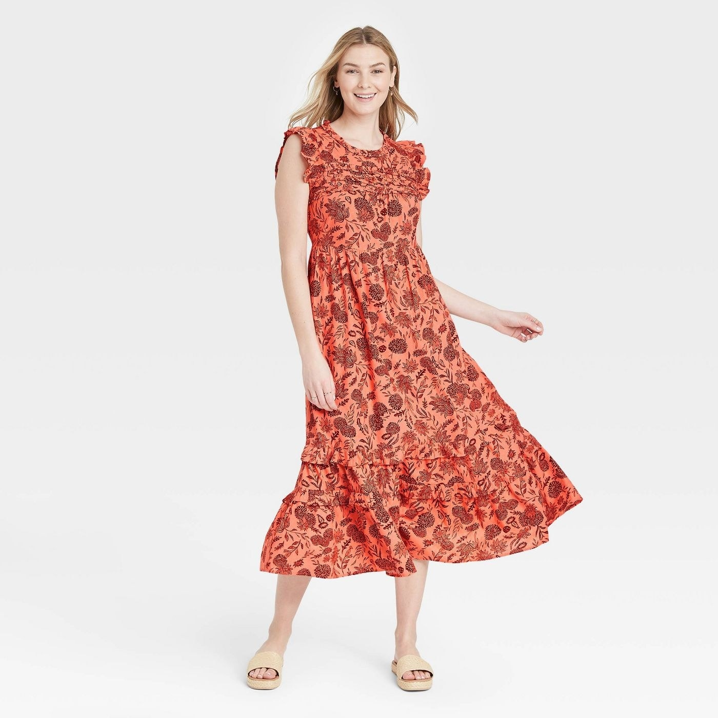 Model wearing orange dress with rust colored floral print