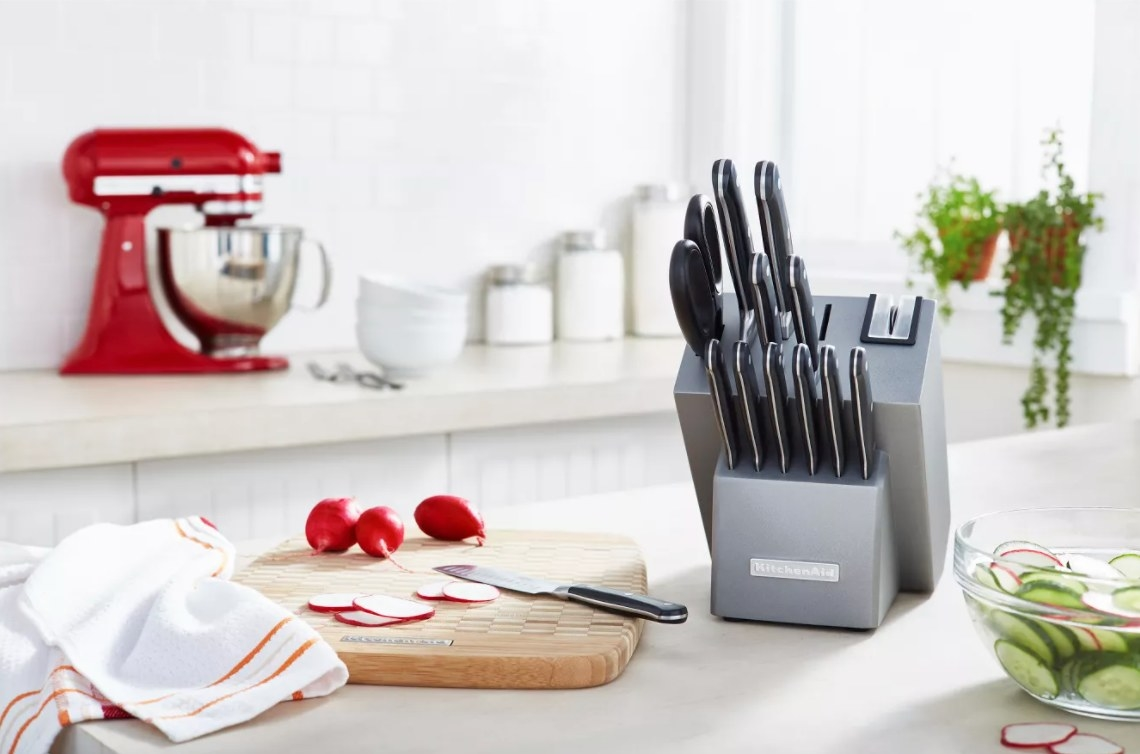 The KitchenAid stainless steel knife set next to a red mixer