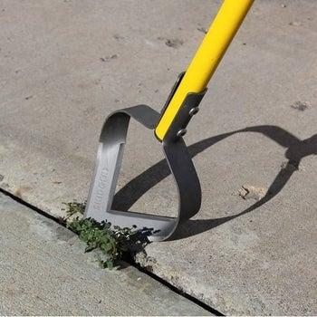 the open teardrop-shaped metal head being used on weeds between cracks in concrete