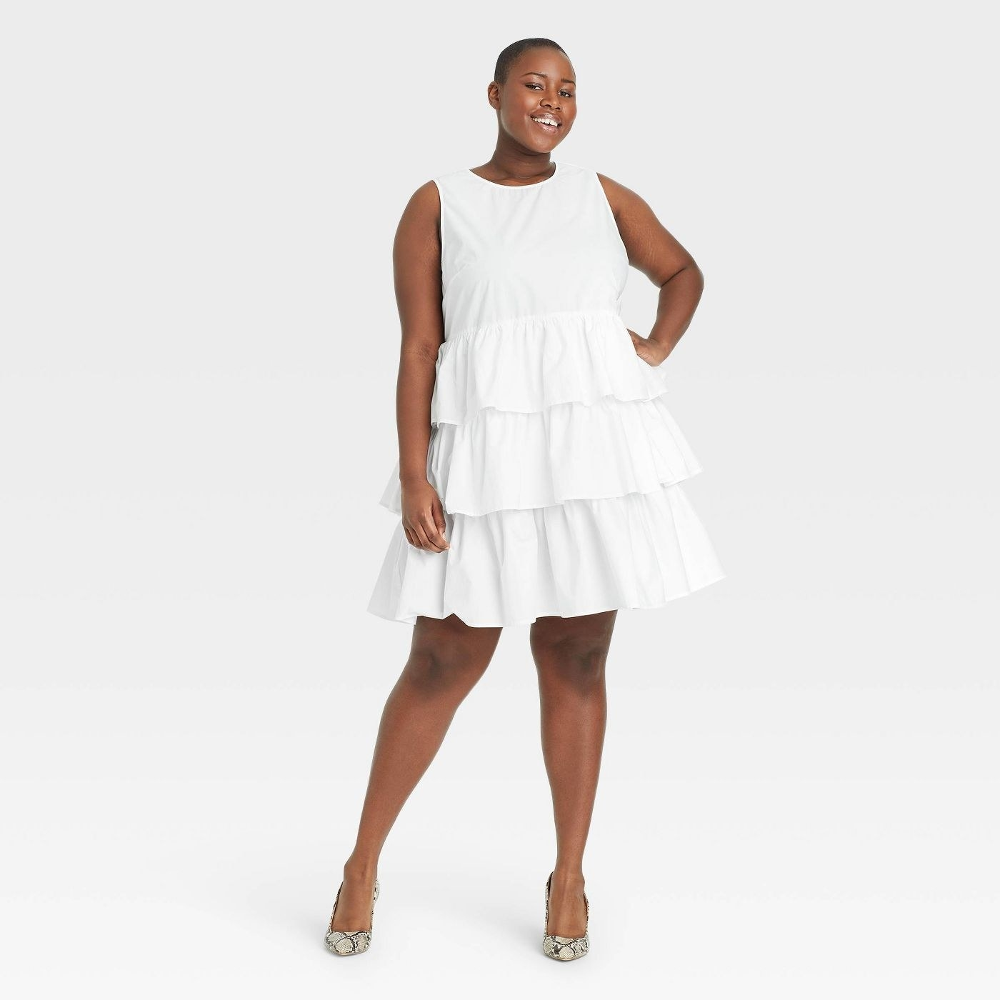 Model wearing white dress ruffle layers, stops above the knee