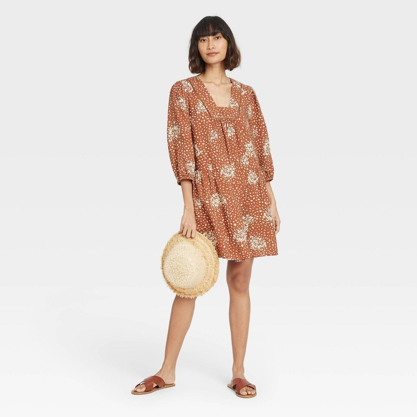 Model wearing dress with cream pattern, stops above the knee