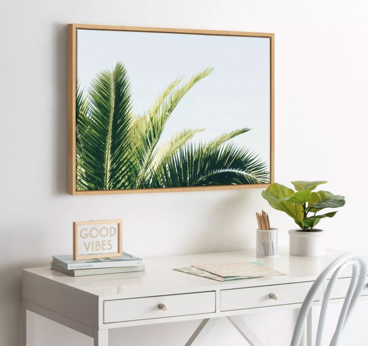 The picture of a tropical palm in a wood frame hung above a white desk