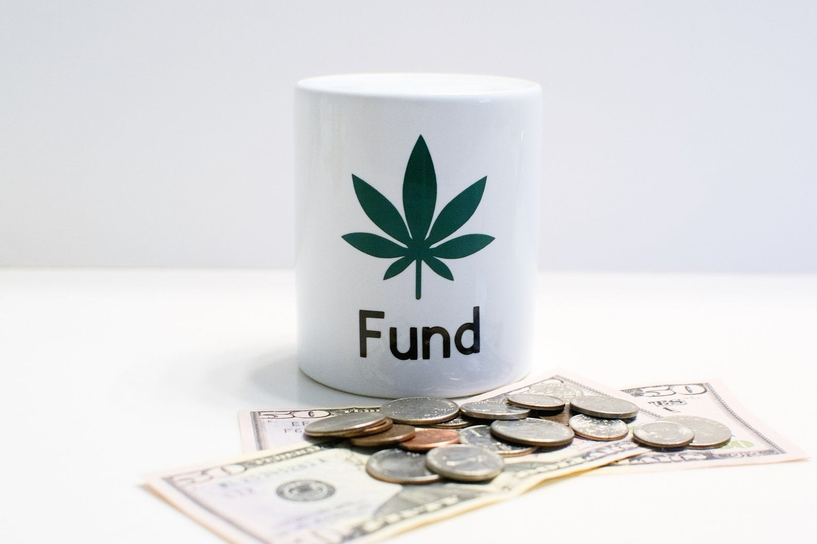 "a white jar that says ""fund"" on it with a marijuana leaf"
