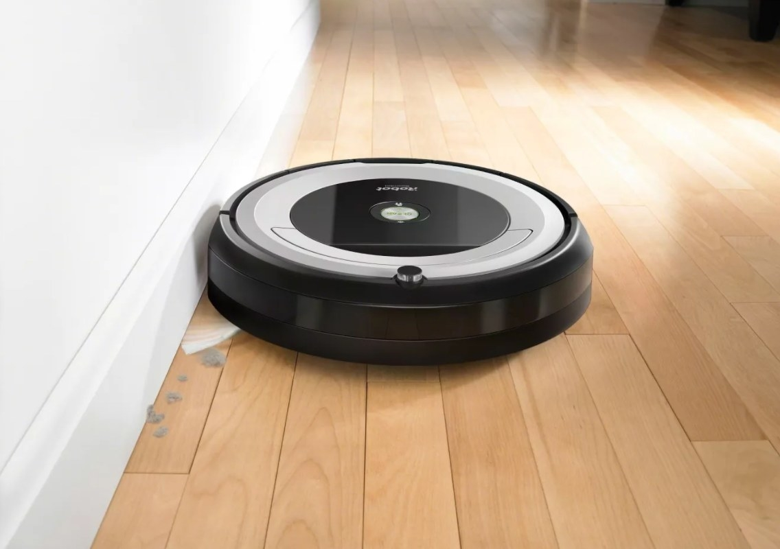 The iRobot Roomba in black and gray on a hardwood floor