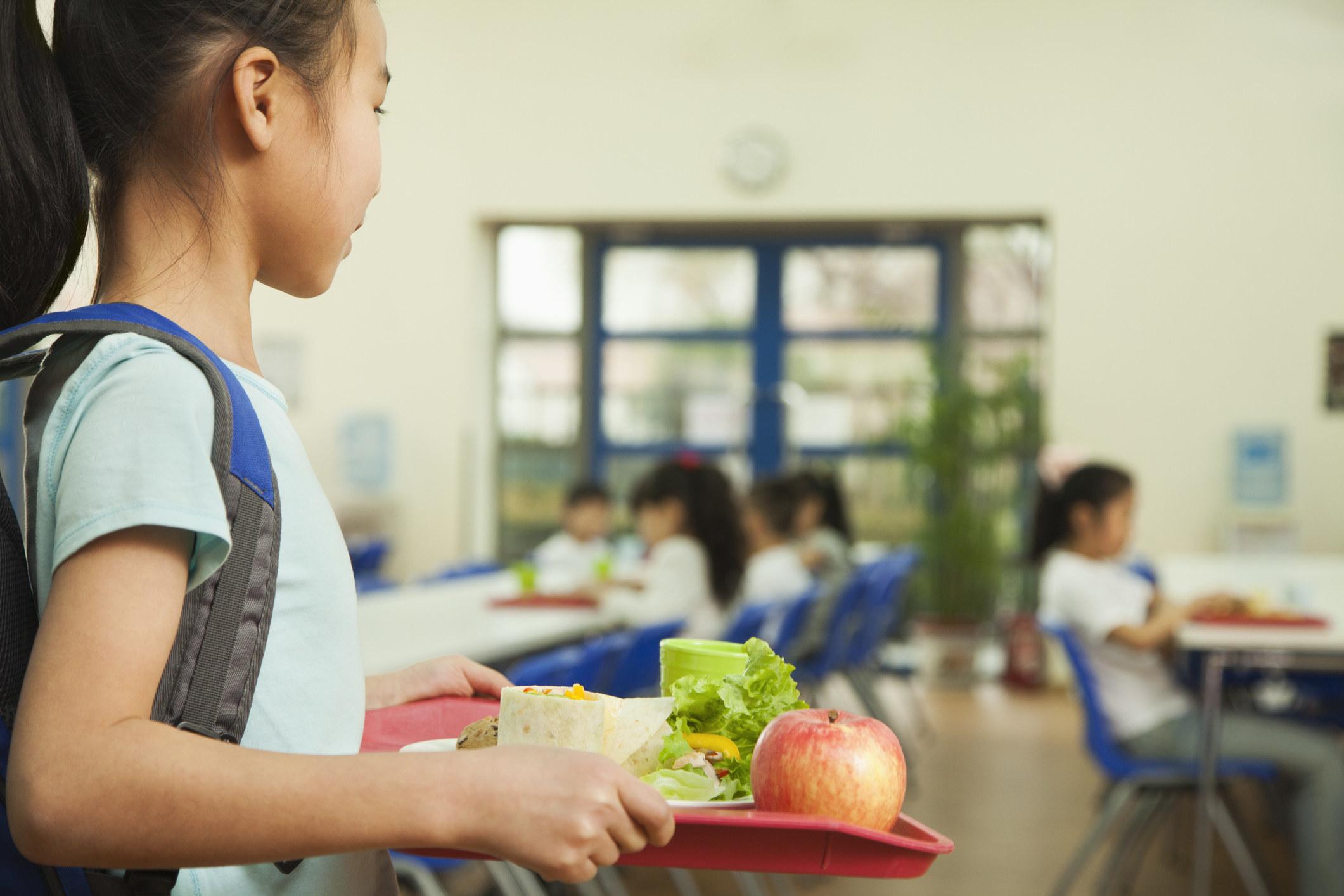 a girl walking a tray through a cafeteria