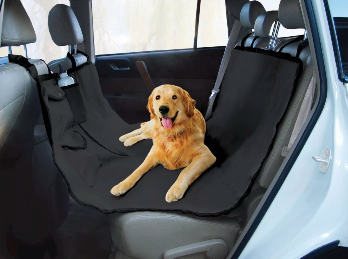 The waterproof hammock dog seat in black holding a golden retriever