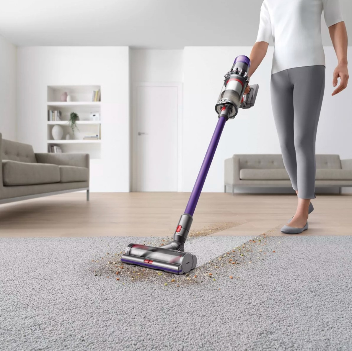 The cordless stick vacuum in purple being used by a model on a dirty carpet