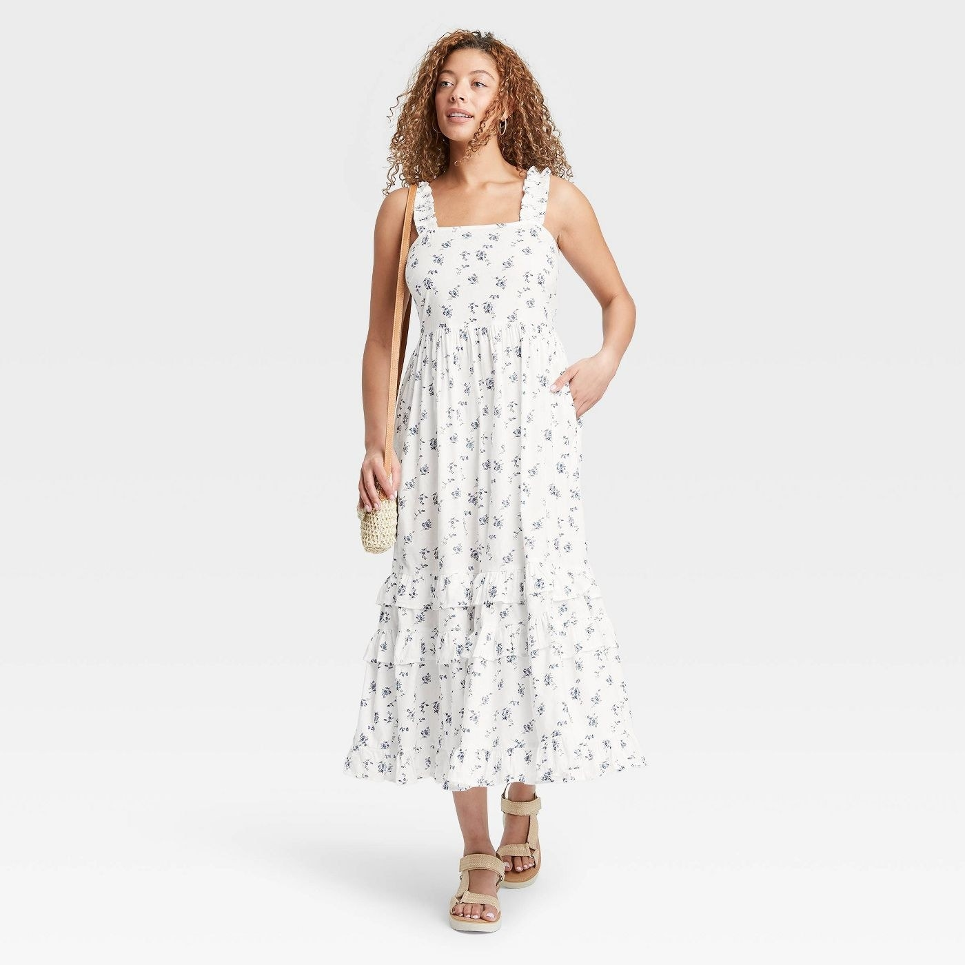 Model wearing white maxi dress with purple flowers