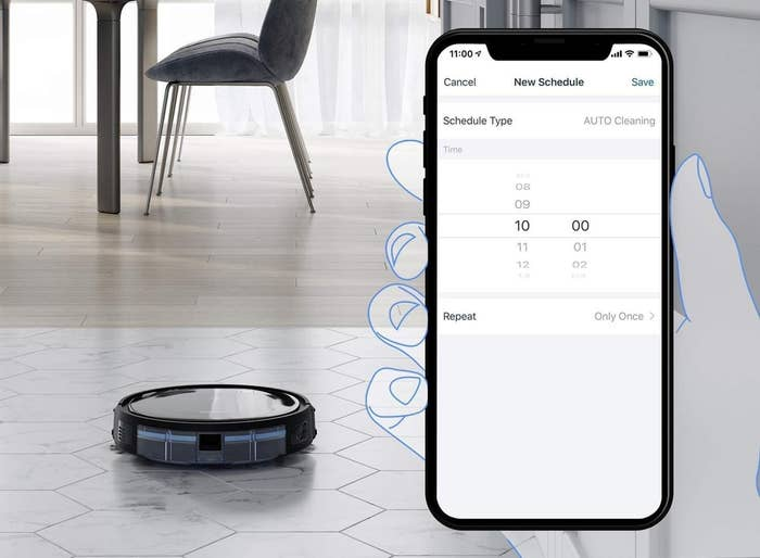 A hand holding a phone in front of the frame while setting the vacuum robot's schedule, which is visible in the background.