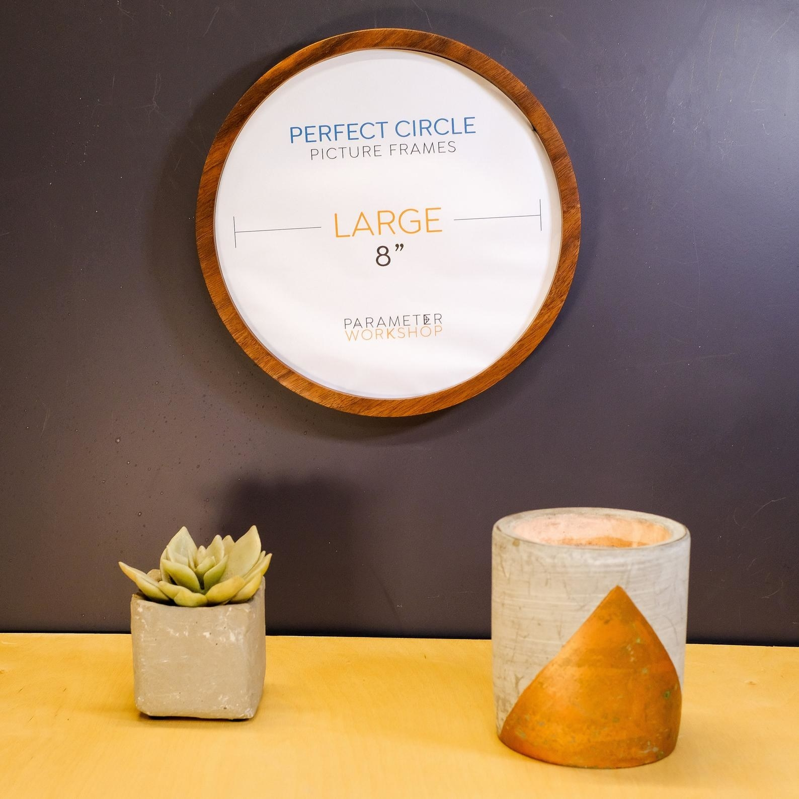 the wooden circle frame on the wall above a succulent and a candle