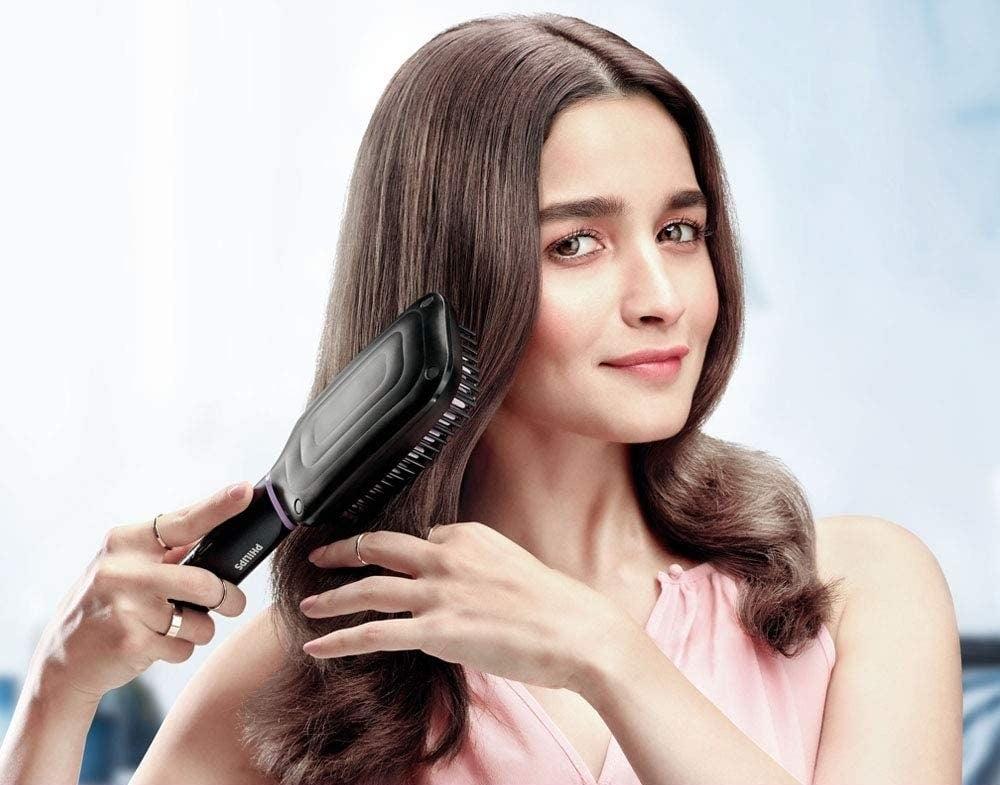 Alia Bhatt using the brush on her hair.