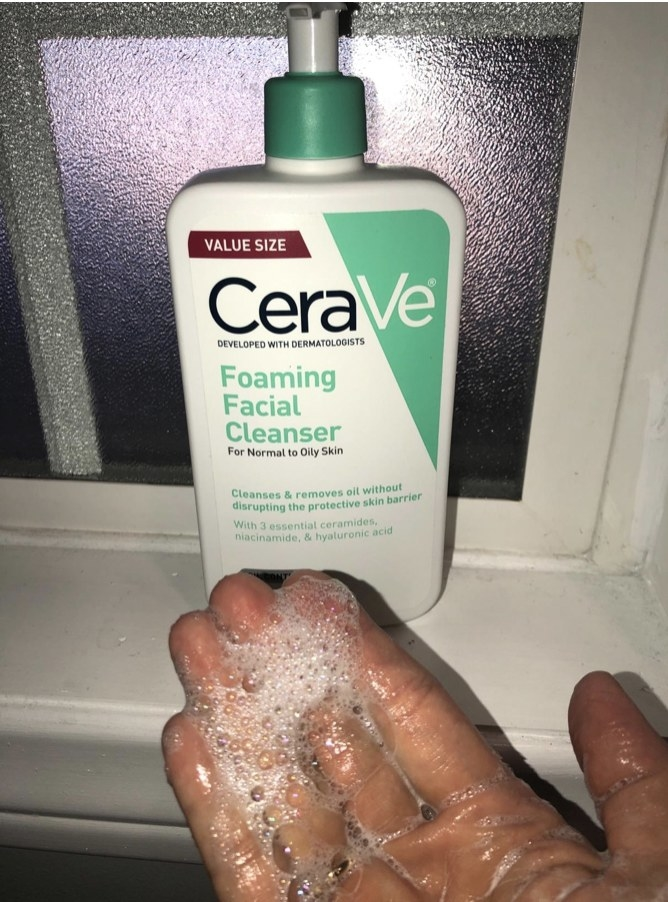 A hand with foaming face wash and a bottle of cleanser