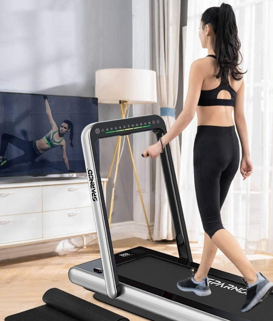 A person using the treadmill in front of their TV.
