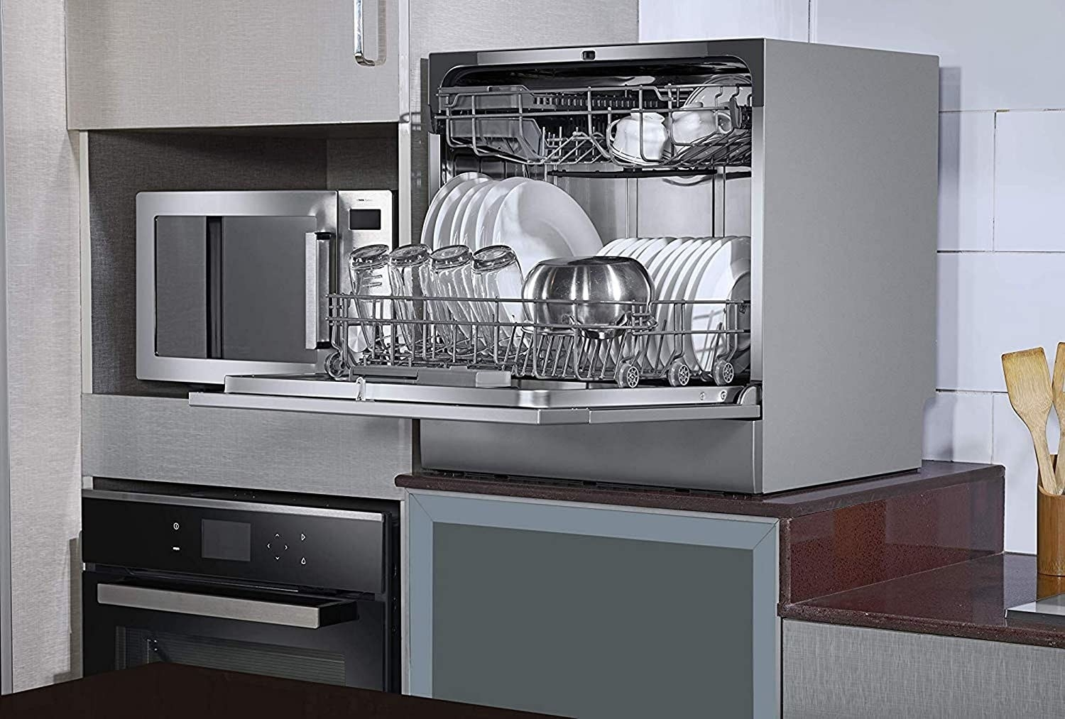 Dishwasher kept in the kitchen with utensils inside.