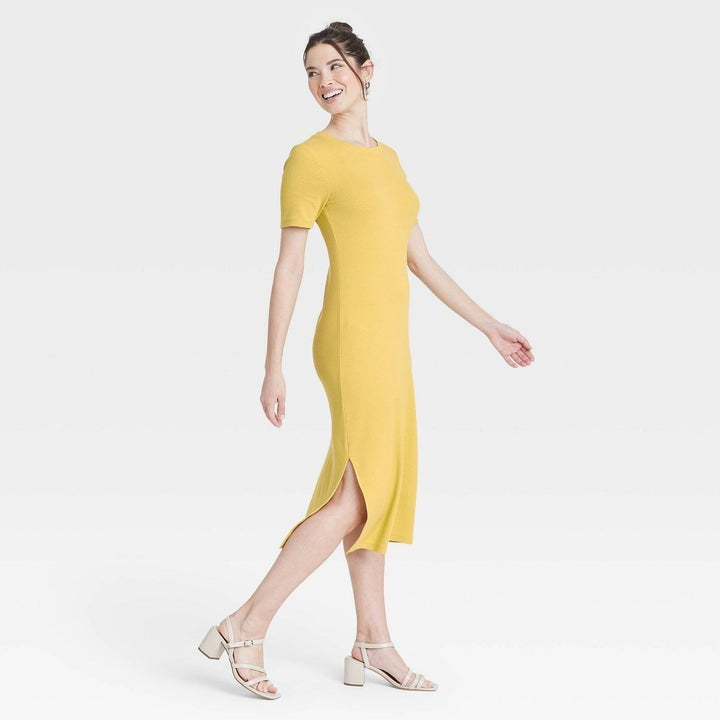 Model wearing yellow dress with two slits on both sides, goes past the knee