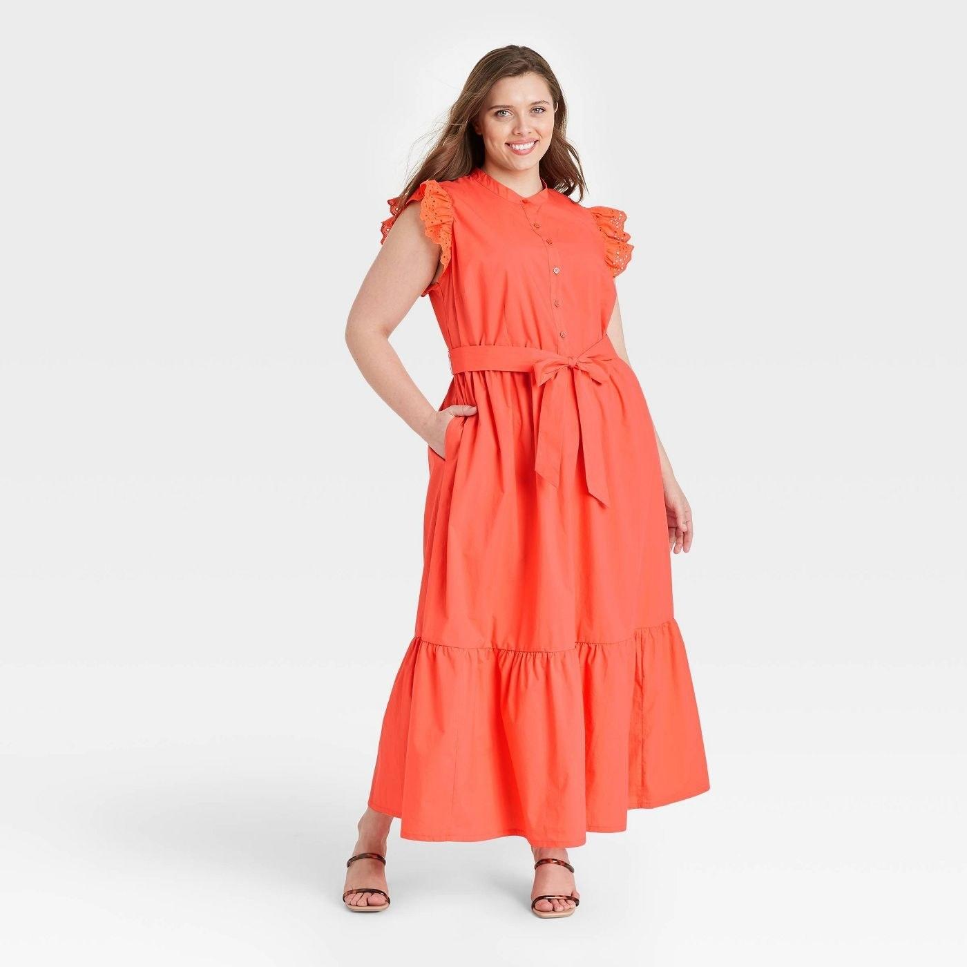 Model wearing orange dress with a tie waist
