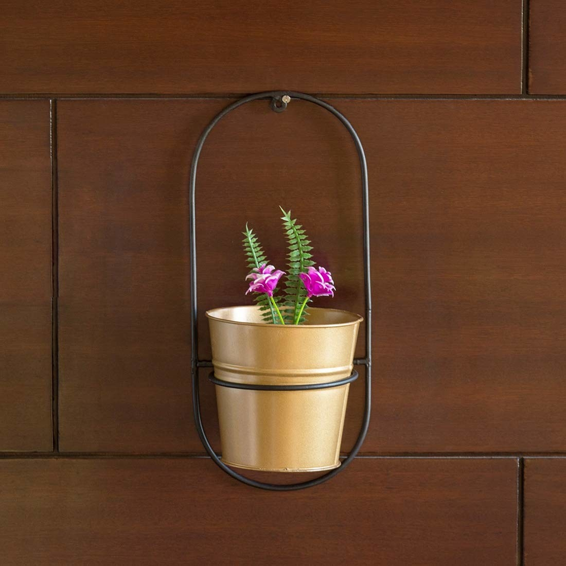 A golden wrought iron planter with an elongated elliptical base hanger also made made of wrought iron in black.