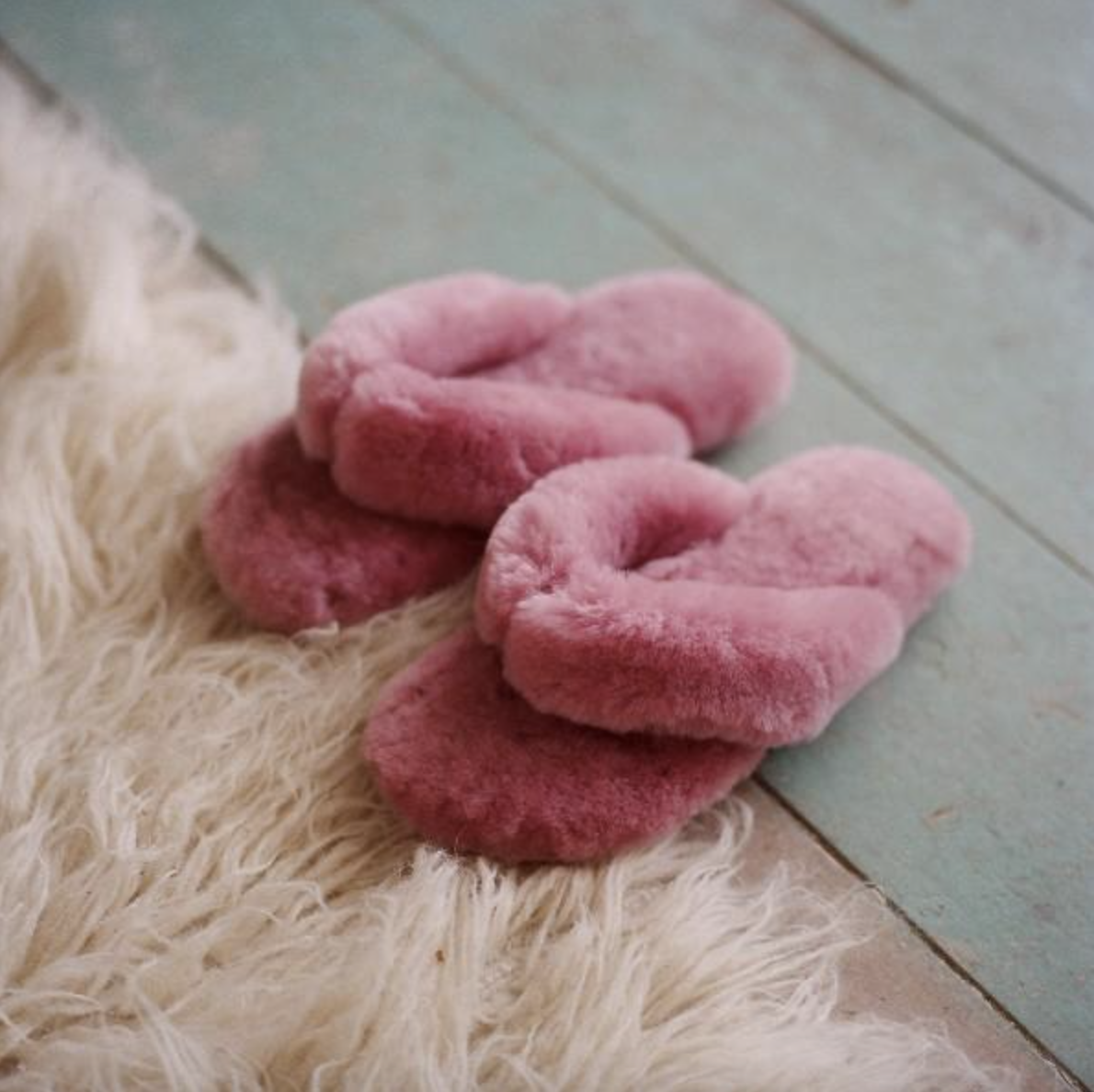 flip-flop style pink sheepskin slippers on a floor