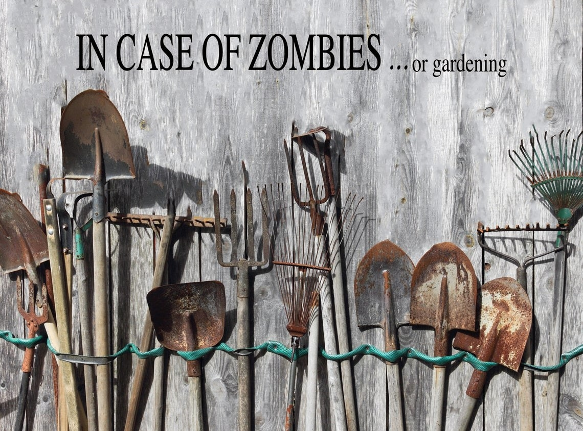 """Decal on shed above several gardening tools that says """"In case of zombies...or gardening"""""""