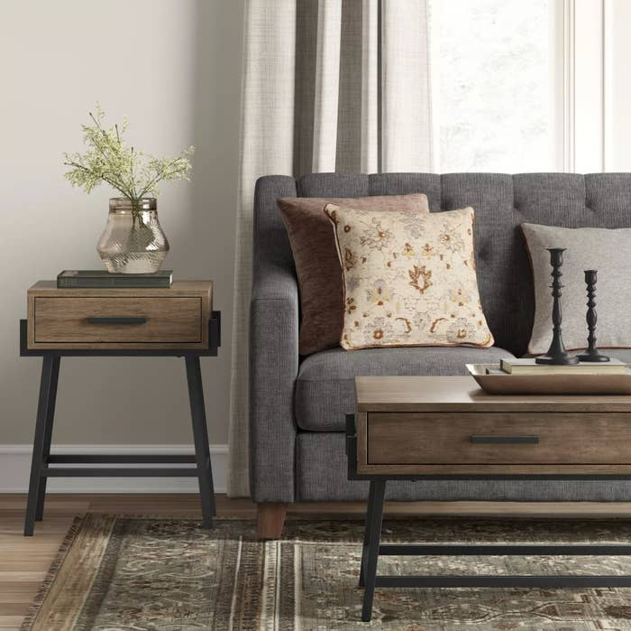 The angled side table in wood next to a gray couch