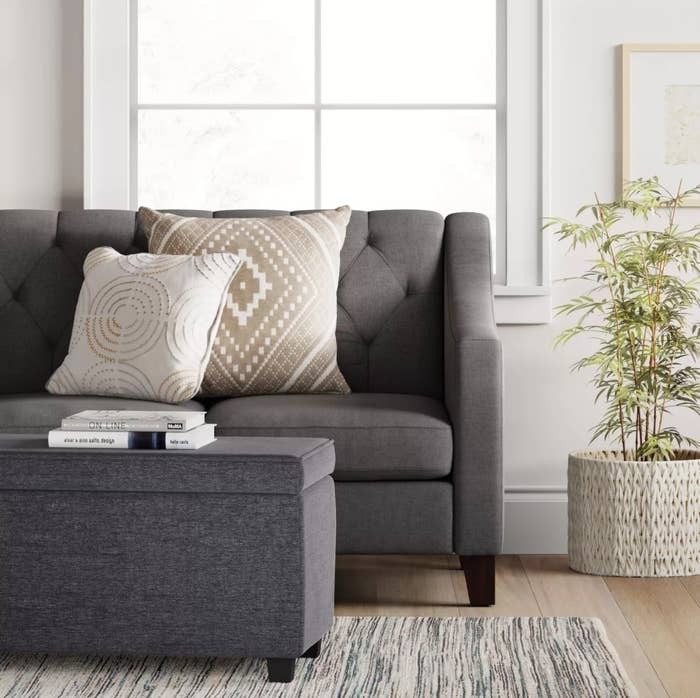 The gray storage ottoman in front of a pleated couch