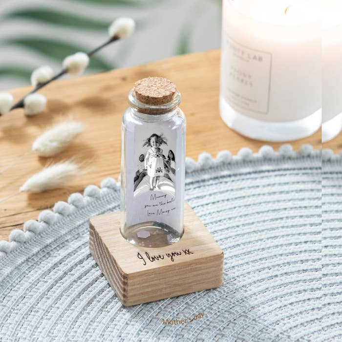 "a tiny glass bottle with a photo of a child and parents inside and a note on top of a wooden stand that says ""i love you"""