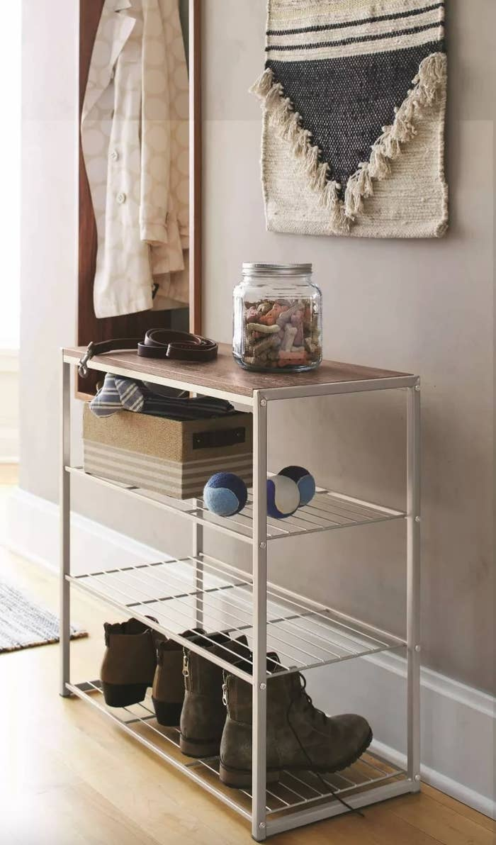 The four-tier shoe rack with a rustic oak finish holding shoes and dog toys and treats