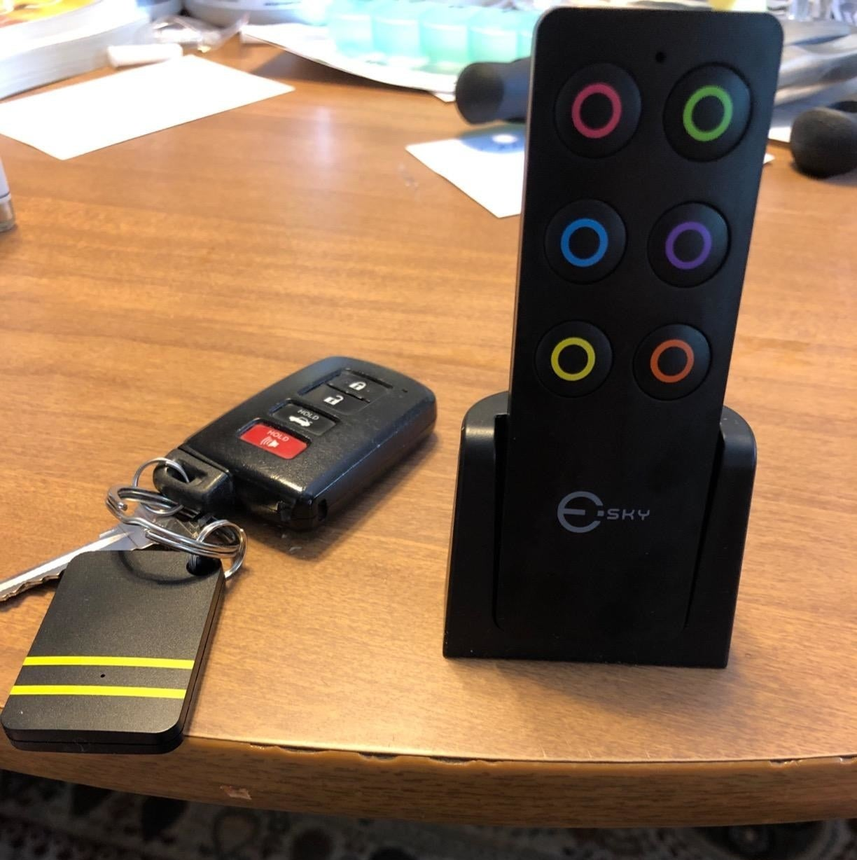 reviewer photo of the remote shaped finder with small colored circles that match lines on the small rectangle pieces with one attached to a set of keys