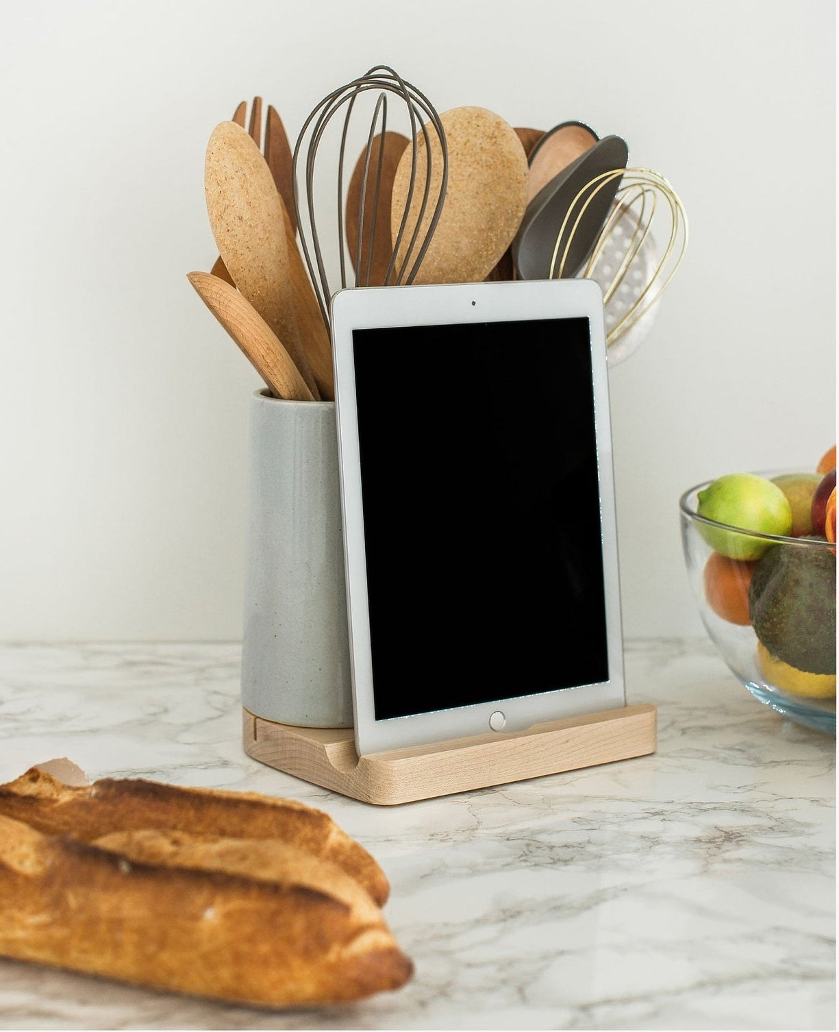 wood base tablet dock and grey ceramic holder with kitchen utensils in it