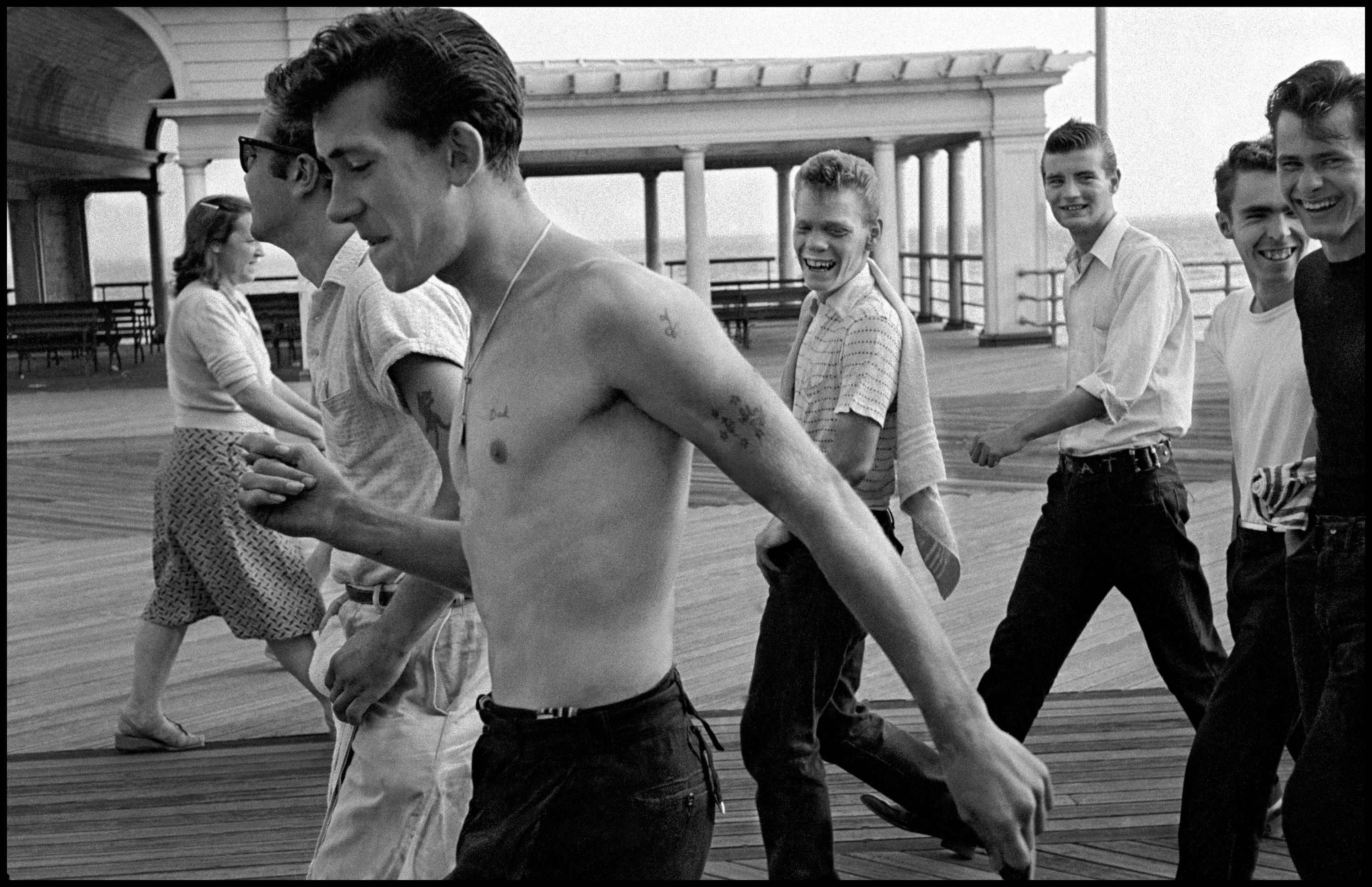 A gang of friends, one with his shirt off and all with ducktail hairdos, on the Coney Island boardwalk in the 1950s
