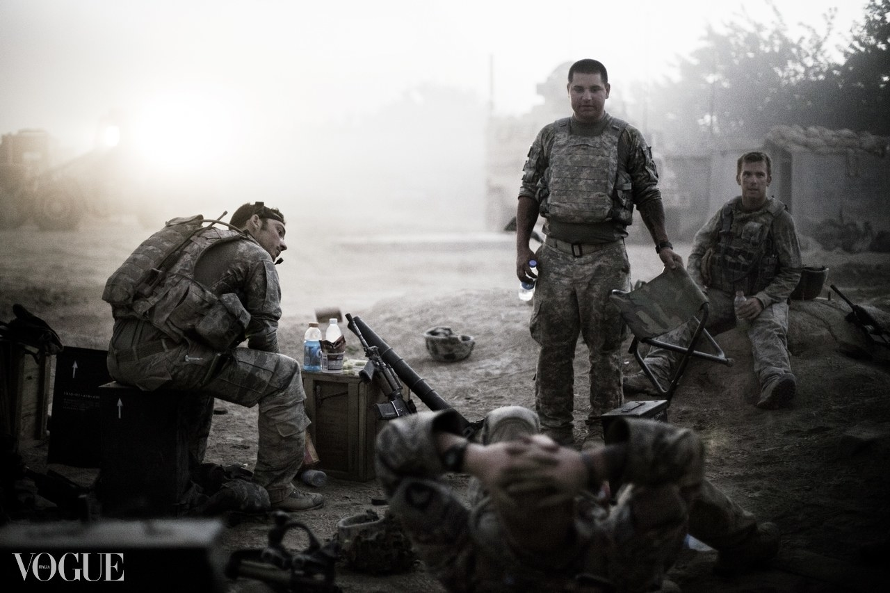 Four soldiers in a war zone relaxing and talking, with one standing and three seated