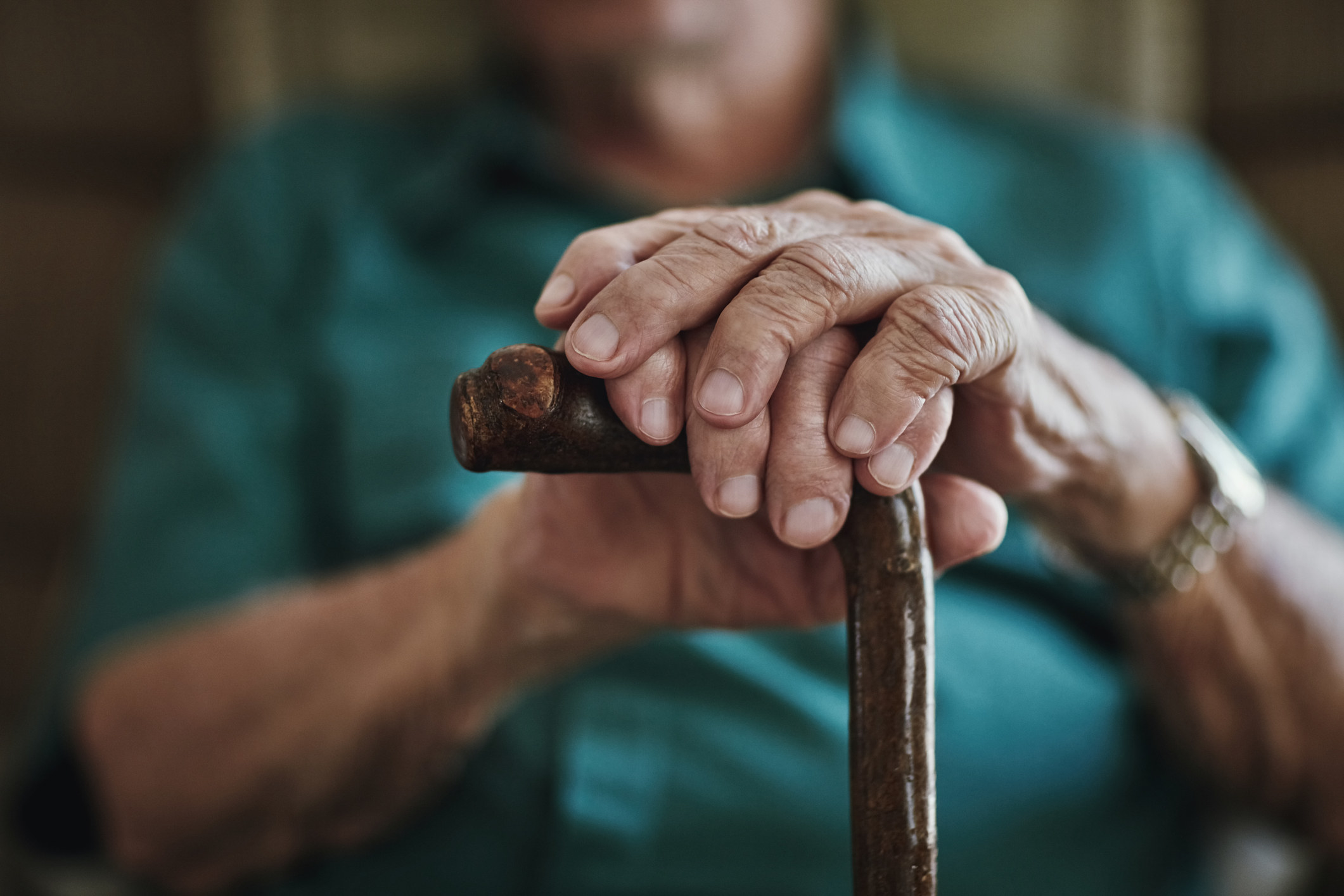 elderly hands holding a cane