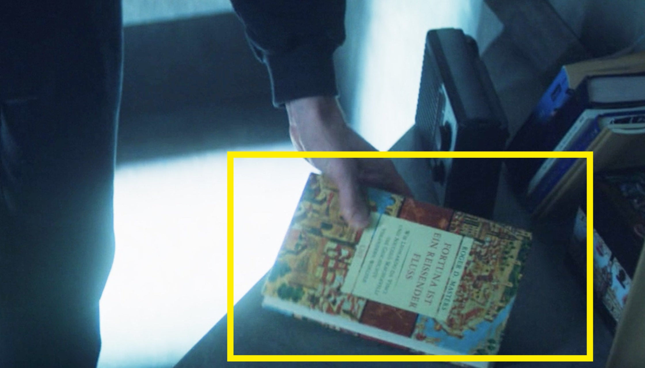 A close-up of Zemo holding his book