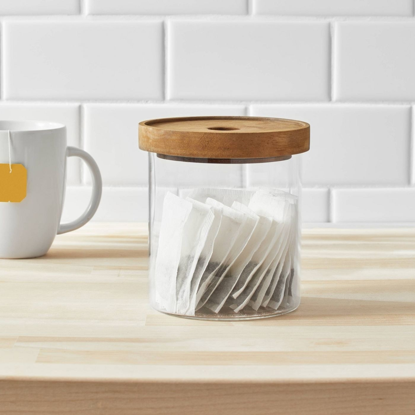 small clear glass container with a wooden lid on a kitchen counter
