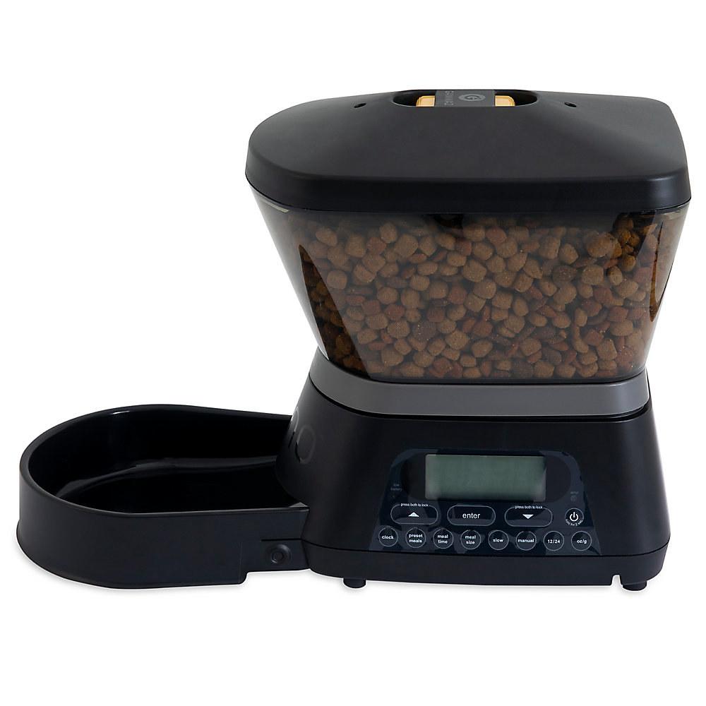 The black plastic pet feeder full of brown kibble